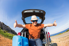 Looking at camera, a cheerful man going away for the weekend by the car with luggage Royalty Free Stock Photo
