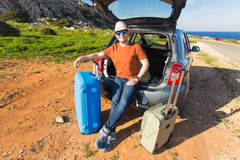 Looking at camera, a cheerful man going away for the weekend by the car with luggage Stock Image