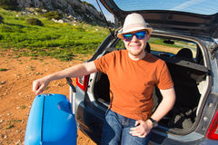 Looking at camera, a cheerful man going away for the weekend by the car with luggage Royalty Free Stock Image