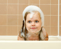 Looking at the camera covered in suds. Happy girl cleaning up in the tub with her head covered in soap bubbles Stock Image