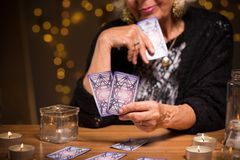 Looking at the cards. Old fortune teller is looking at the cards Stock Photo