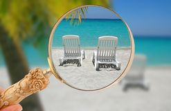 Looking into a Caribbean getaway. Hand holding a magnifying glass or loop, looking in on  tropical beach chairs in sand at the shoreline in the Caribbean with Stock Image