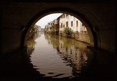 Looking Through the Circle. Reflection through a half round tunnel of a canal lined with old houses, in old Suzhou, China Stock Photos