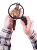Looking at clock through loupe. Man look at old clock through big loupe Stock Images