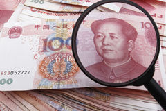 Looking close on a Chinese 100 RMB banknote. Looking close on a Chinese 100 RMB banknote with a magnifying glass, lots of Chinese money underneath Stock Photography