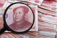Looking close at a Chinese 100 RMB banknote. Looking close at a Chinese 100 RMB banknote with a magnifying glass, lots of Chinese money underneath Stock Images