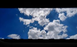 Looking at clouds through the window stock photography
