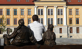 Looking for college. Man standing and dreaming on bench looking towards university accompanied by statues Royalty Free Stock Images