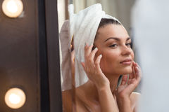 Looking at complexion. Young woman is looking at her complexion after bath Stock Photo