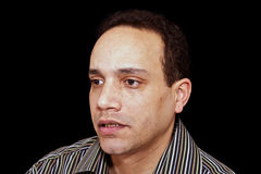 Looking concerned. Concerned looking portrait of african american male wearing striped shirt against black background Royalty Free Stock Photo