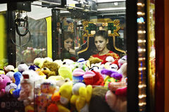 Looking at the crane machine. 2 teenagers are looking  inside the crane machine Stock Photography
