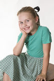 Looking cute. Young girl sitting with face resting on hand smiling at the camera Royalty Free Stock Images