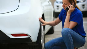 Looking at a damaged vehicle. Woman blonde inspects car damage after an accident stock footage