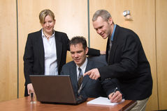 Looking at data. 3 business people around a laptop in a meeting pointing stock images