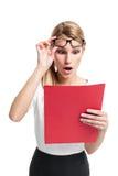 Looking de secretaria Surprised bonito a una carpeta roja Foto de archivo