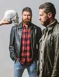Looking deep into eyes of your fear. Man brutal bearded hipster looking at skull symbol of death. Overcome your fears stock images