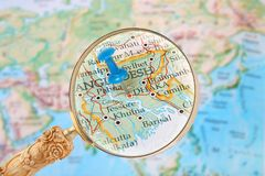 Looking in on Dhaka, Bangladesh. Blue tack on map of the world with magnifying glass looking in on Dhaka, Bangladesh stock photo