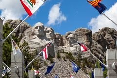 Mount Rushmore with State Flags. Looking through a display of state flags up to the four presidential faces carved into Mount Rushmore in South Dakota on a stock photos