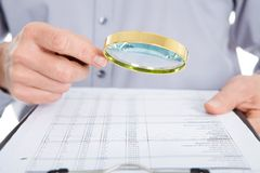 Looking at document through magnifying glass Stock Image