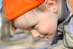 Looking down. Little boy in orange sideward turned cap looking down Stock Images