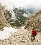 Looking Down from Above. A hiker examines the route to the valley from atop the summit of a mountain in the Alps of northern Italy Stock Photo