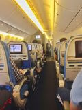 Looking down the aisle on an aeroplane. Looking down the aisle on an aeroplane, you see rows of seats filled with passengers. Seats all have a display in the Royalty Free Stock Photo