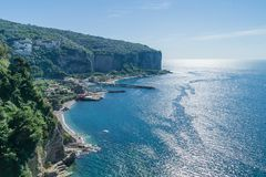 Looking down on Amalfi coast at Vico Equense, near Sorrento in Italy. Showing houses nestling in the steep cliffs, beaches below and miles of sparkling blue Royalty Free Stock Images
