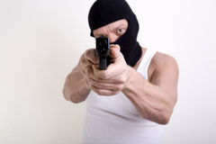 Looking down the barrel. Armed criminal with a handgun pointed at camera so that one is looking down the barrel of a gun Stock Images