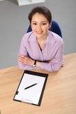 Looking down on beautiful Asian woman at desk Royalty Free Stock Images