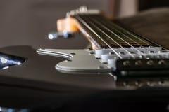 Looking down electric guitar strings. Looking down a black electric guitar strings stock photo