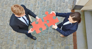 Looking down on business people with jigsaw puzzle pieces Royalty Free Stock Image