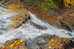 Looking Down Buttermilk Falls. Buttermilk Falls, a waterfall in Ohio's Cuyahoga Valley National Park, cascades down rock ledges with colorful autumn leaves Stock Photography