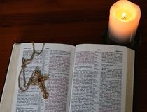 Candle glowing near gold cross on open Bible royalty free stock photo