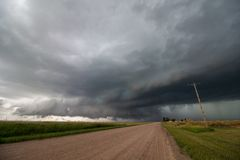 Looking down a dirt road at a supercell thunderstorm. Looking down a dirt road at a supercell thunderstorm updraft with a low dark cloud base stock photo