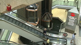 Looking down at elevators and escalators within mall. A view or scene of Shopping stock video footage