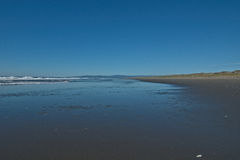 Looking down flat beach with dark blue reflection in sand Royalty Free Stock Photo