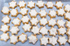Looking down on flat lay of home baked imperfect star shaped cin. Namon Swiss or German style Christmas cookies - known as Zimtsterne royalty free stock image
