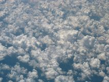 View of puffy white cumulus clouds from an airplane royalty free stock image