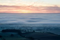 Looking down on fog and temperature inversion from the Malvern Hills. In the English countryside. With sunrise on a winters day. stock images