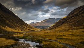 Looking down Glen Etive. Looking down valley Glen Etive in the Scottish Highlands with a winding road and river Stock Photo