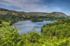 Looking down on Grasmere. View through ferns and other vegetation towards lake Grasmere in the English Lake District national park Royalty Free Stock Image