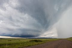 Looking down a gravel road at a supercell thunderstorm approaching. With mountains on the horizon stock images