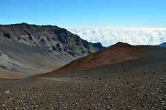 Looking down in the Haleakala Crater while clouds are being blown over the mountain ridge, Maui island, Hawaii royalty free stock photo