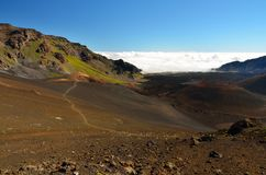 Looking down in the Haleakala Crater while clouds are being blown over the mountain ridge, Maui island, Hawaii Stock Image