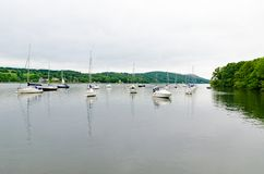 Boast and yachts moored on a still Lake Windermere. Looking down Lake Windermere at the moored boast and yachts on a calm cloudy day with green trees to both Stock Photo