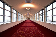 Looking down a long Corridor of red carpet windows on either side and lights over the ceiling with double doors at the end. Looking down a long Corridor with red Royalty Free Stock Photography