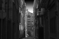 Looking down a long dark back alley. With a lone refuse worker at the bottom Stock Photo