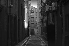 Looking down a long dark back alley stock photography