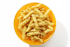 Looking down at a plate of cooked penne pasta with spices Royalty Free Stock Images