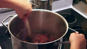 Ground beef making stew. Looking down into a pot of hot ground beef being stirred in a giant metal pot stock footage